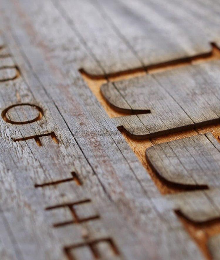 Træskilte på planke med tekst